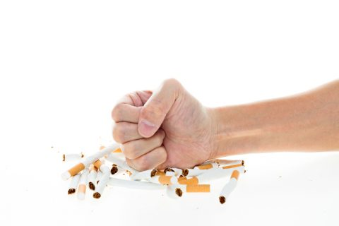 Man fist destroying cigarettes against white background. stop smoking concept.